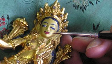 Het beeldje is vervolgens door Carmen schoongemaakt en wordt nu met de juiste kleuren en met echt goud beschilderd volgens de tibetaanse traditie. Ook al is het een klein beeldje, met zoveel detail kost dit al gauw 3 tot uur werk.